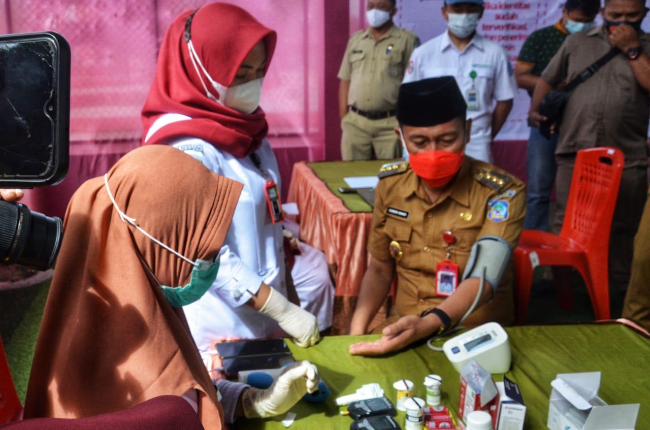 Petugas kesehatan saat memeriksa tekanan darah Bupati Iskandar Kamaru