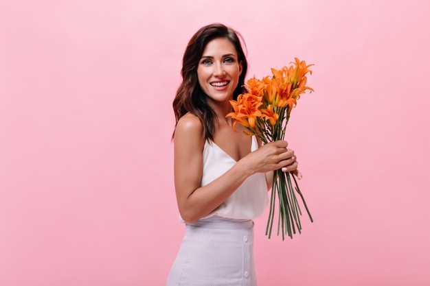 lady-white-outfit-is-smiling-holding-bouquet-flowers-beautiful-woman-posing-camera-with-cute-orange-flowers-isolated-background_197531-18014